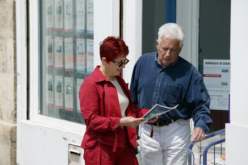 Couple de seniors devant une agence de location