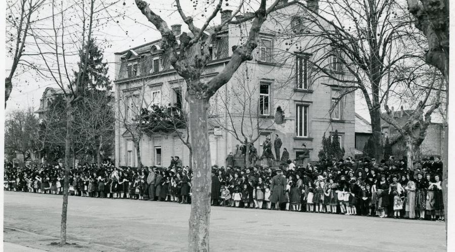 Au bord de l'avenue, la foule est compacte. Les maisons portent encore les stigmates des combats.