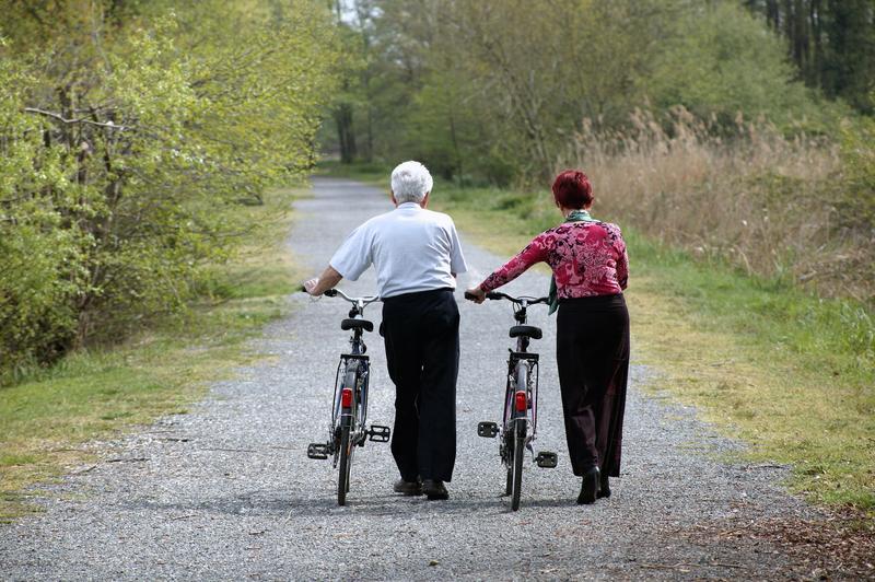 Deux personnes âgées qui marchent avec des vélos